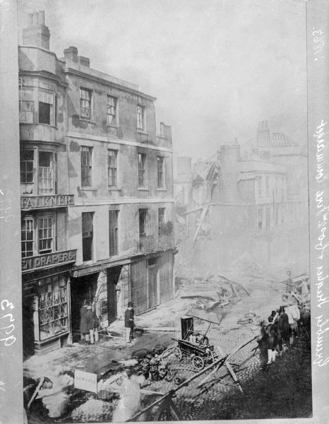 GRIMBLY HUGHES & COMPANY, Cornmarket Street, Oxford, Oxfordshire. Showing the remains of a shop destroyed by a second fire in 1863. A crowd has gathered. A hand-operated fire engine remains in the middle of the road. Henry Taunt