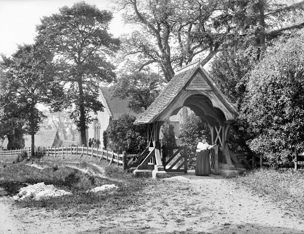 ST MARYS CHURCH, Aldworth, Berkshire. Looking towards the church which is visible through the trees with a woman passing through the lychgate in the foreground. Photographed in 1895 by Henry Taunt.