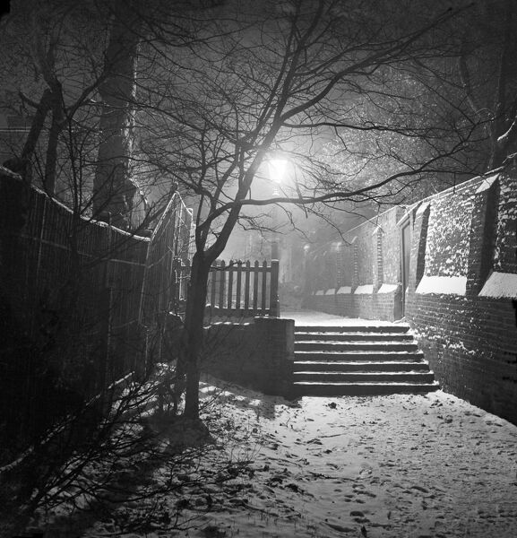 HAMPSTEAD, London. A set of steps in the snow in a wide alleyway at night with a lit street lamp behind. John Gay. Date range: 1960-1965