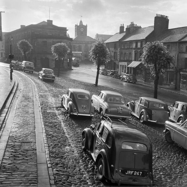 MARKET STREET, Alnwick, Northumberland. Looking west along Market Street towards the Northumberland Hall and Town Hall beyond, showing cars parked on cobbles in the foreground. Photographed by John Gay during the 1950s