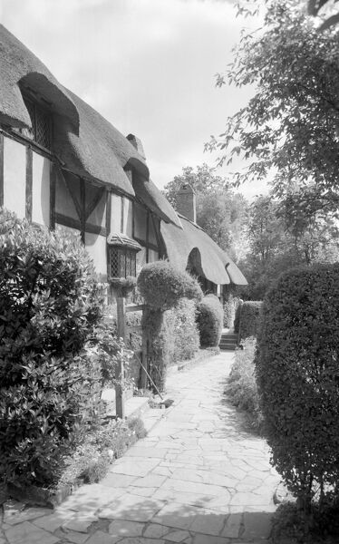 ANNE HATHAWAY'S COTTAGE, Shottery, Stratford upon Avon, Warwickshire. Anne Hathaway's Cottage in Stratford-upon-Avon, looking along the pathway at the front of the cottage. This half-timbered house dates in part from the 15th century