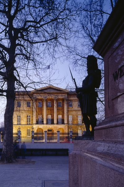 APSLEY HOUSE, London. View of the house floodlit at dusk with the base of the Wellington statue to the right