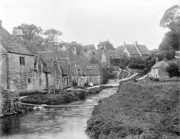 ARLINGTON ROW, Bibury, Gloucestershire. Looking up the well-known row of Cotswold stone cottages on the river Coln. These were converted into dwellings in the early 17th century from a monastic sheephouse dating to c.1380 with ten bays of cruck trusses
