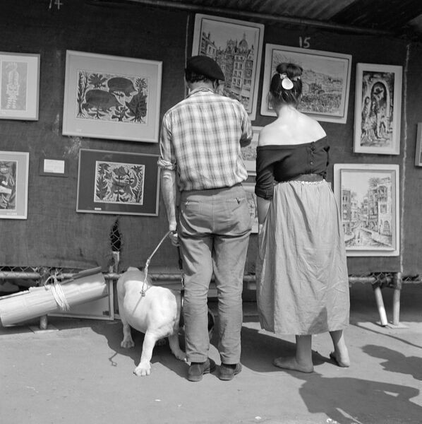 HEATH STREET, Hampstead, London. The rear view of a man in shirt sleeves and beret with a dog on a lead and a woman in an off-the-shoulder top looking at paintings at an open air art exhibition. John Gay. Date range: 1960-1965