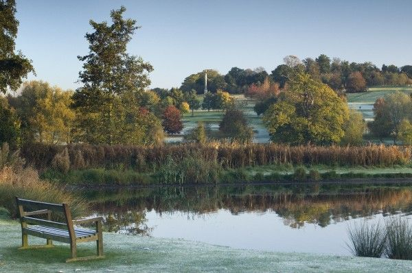 AUDLEY END HOUSE AND GARDENS, Essex. Garden view showing bench by the pond. Autumnal frost settles on the surrounding landscape with Lady Portmouth's Column in the distance