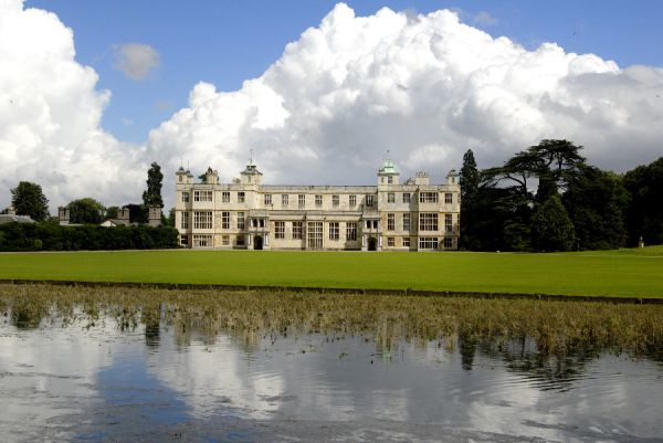 AUDLEY END HOUSE AND GARDENS, Essex. The West front of the house viewed from across the River Cam with a mountain of cloud behind