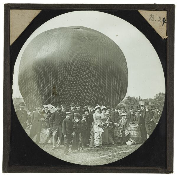 Tales of balloon flight. A smartly dressed group has gathered to pose for a photograph with a near-inflated balloon