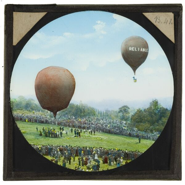 A hand-coloured lantern slide showing Shadbolt's balloon 'Reliance' taking off from the grounds of Alexandra Palace, with large crowds watching