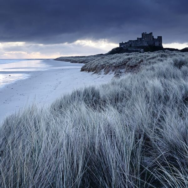 BAMBURGH CASTLE, Northumberland. Storm clouds hover above the castle and sand dunes