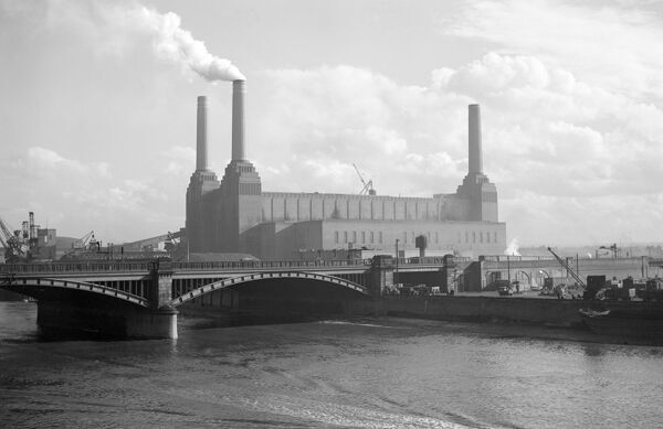 BATTERSEA POWER STATION, London. A view looking south east from Chelsea Bridge towards the power station (the building's fourth chimney was added later) with Grosvenor Bridge before it. The power station was designed by Sir Giles Gilbert Scott