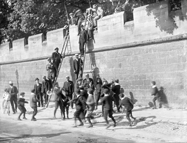 Beating the Bounds, Longwall Street, Oxford. Boys scramble for coins at Longwall during the annual ceremony of beating the bounds, which reinforces knowledge of the parish boundary. The ceremony, which takes place on Ascension Day, is led by the parish priest