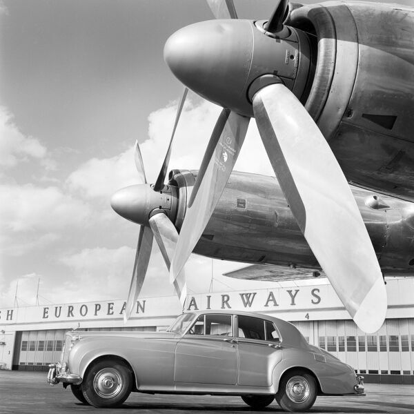 HEATHROW AIRPORT, B E A Aircraft Hangar, London. A Bentley car parked on the runway in front of the British European Airways buildings at Heathrow Airport with the propellers of an aircraft visible in the foreground. Photographed by John Gay
