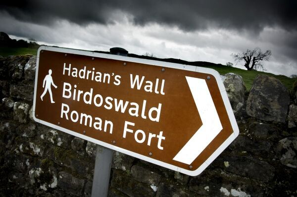 HADRIAN'S WALL: BIRDOSWALD ROMAN FORT, Cumbria. Brown tourist signage pointing to Birdoswald with overcast skyline in the background. hadrian