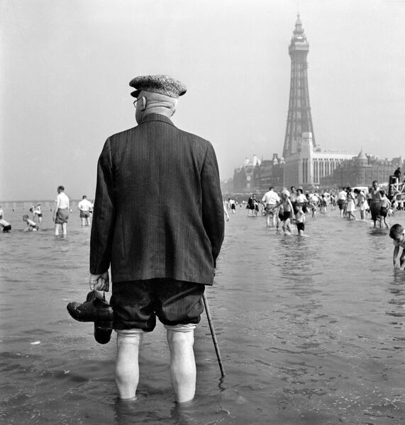BLACKPOOL, Lancashire. An elderly man on holiday paddling in the sea, with Blackpool Tower in the background. Date range 1946-1955. John Gay