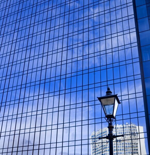 Blue sky reflected in glass tower block with gas lamp in foreground, Broad Street, Birmingham, West Midlands