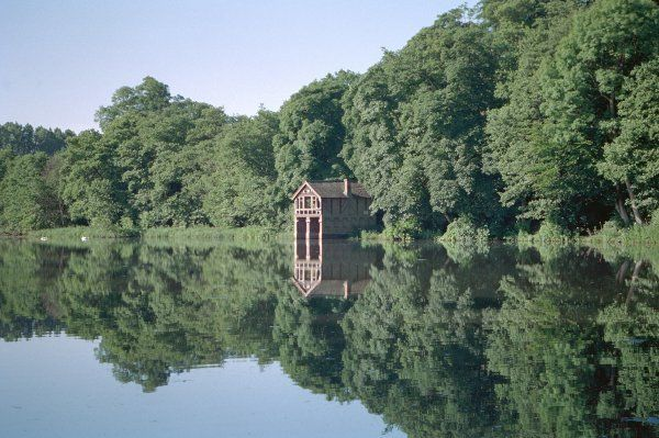 Picturesque shot of the boat house and surrounding trees being reflected in the water. IoE 362660
