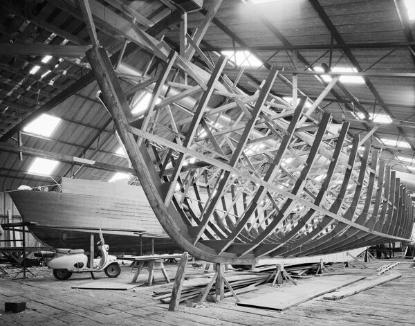 F B Wild's Boatyard, Horning, Norfolk. Interior view. Two boats at different stages of construction, and a parked moped. Photographed by Hallam Ashley 1963