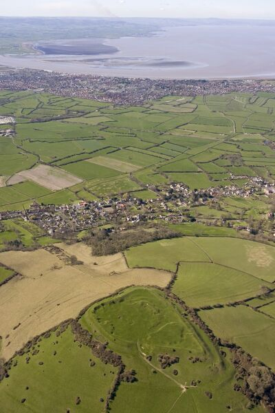 "BRENT KNOLL HILLFORT, Somerset, ST340509 (RSM 24001). Aerial view. An Iron Age fort with multiple ramparts on a hill overlooking the Somerset Levels. Once known as the ""Isle of Frogs"", Brent Knoll has associations with the quest of Ider"