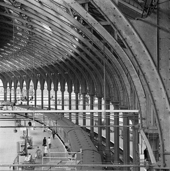 BRIGHTON STATION, East Sussex. An elevated interior view showing a curving row of columns supporting the roof of the train shed at Brighton station with a train visible waiting at the platform beneath. Photographed by John Gay. Date range: 1967-1985
