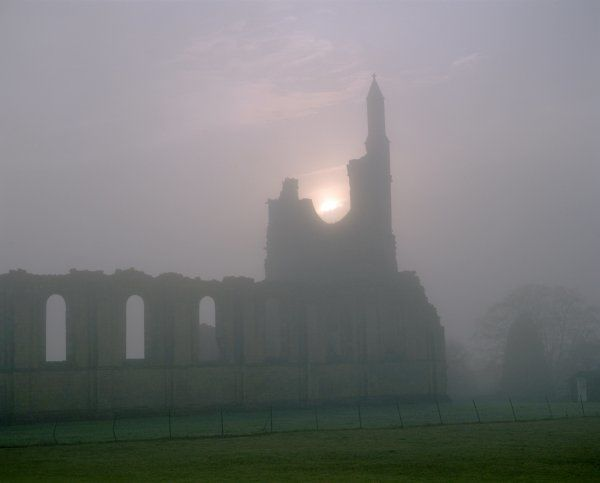 BYLAND ABBEY, North Yorkshire. Silhouette of the West front of the church in fog at sunset