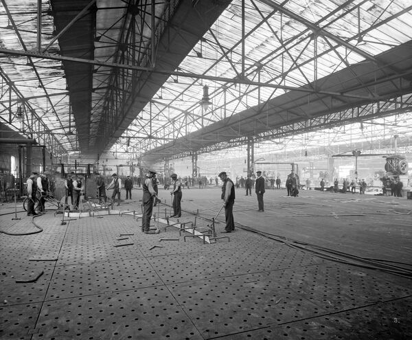 Cammell Laird & Co shipyard, Birkenhead. Interior view showing men working in the ship shed. One of a series of photographs of Cammell Laird works. Bedford Lemere. June 1913