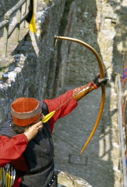 CARISBROOKE CASTLE, Isle of Wight. Re-enactment event. Archer with bow and arrow on the battlements