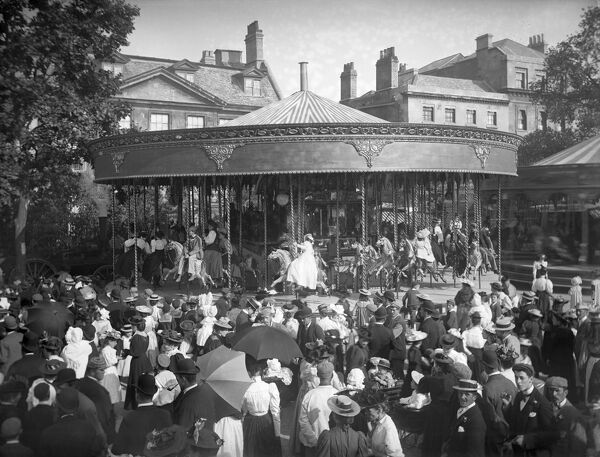 St Giles Fair, Oxford. A crowd of people gathered around a carousel ride in St Giles during the annual fair, held at the beginning of September. Photographed by Henry Taunt in 1895