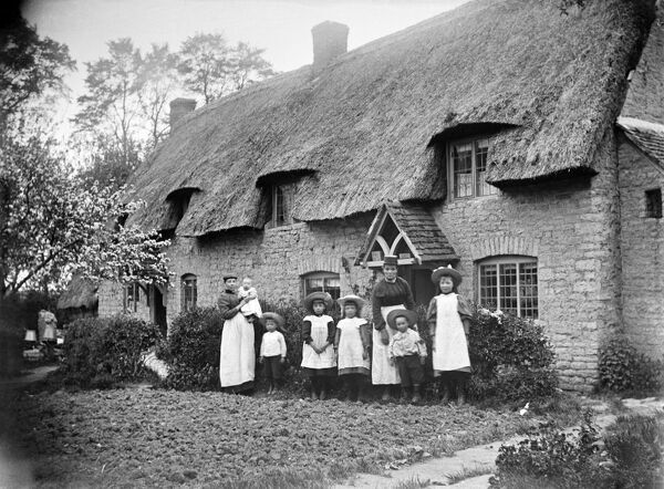 A thatched cottage, Marsh Gibbon, Buckinghamshire. A group of people pose for the camera in front of thatched cottages. Photographed by Alfred Newton and Son 1904