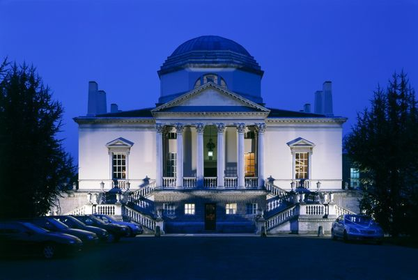 CHISWICK HOUSE, London. View of the Palladian style entrance, floodlit at dusk