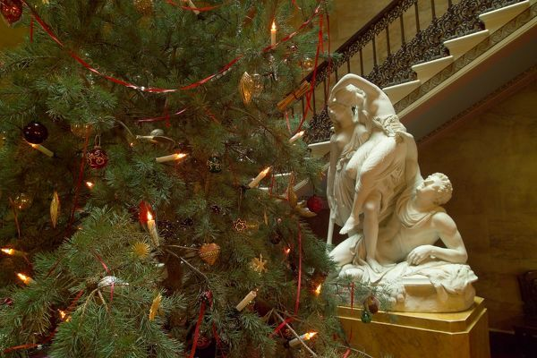 OSBORNE HOUSE, Isle of Wight. Interior view. Christmas at Royal Osborne. Christmas tree in stairwell with statue behind. Some items shown maybe on loan from the Royal Collection