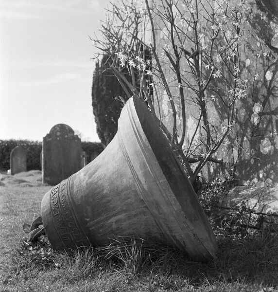 A church bell lying on its side in a churchyard in Somerset. Photographed by John Gay in April 1953