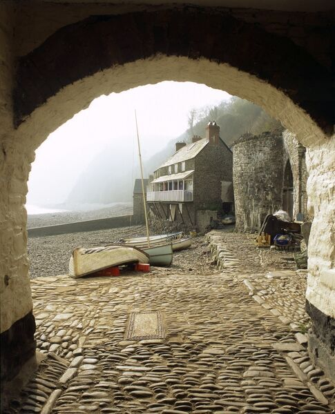 CLOVELLY, Devon. View through arch to the harbour with cobbled street and boats on the shingle beach