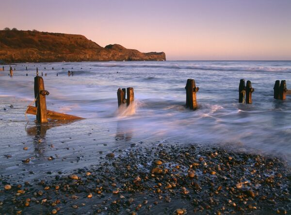 SANDSEND, North Yorkshire. A view at sunrise looking North West across the groynes towards Sandsend Ness