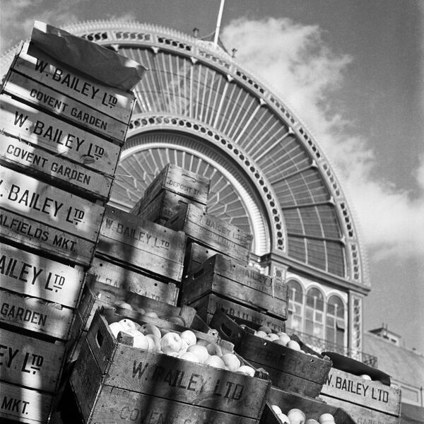 COVENT GARDEN, London. Looking up at the arched iron and glass facade of Covent Garden market's Floral Hall, with piles of fruit crates belonging to W. Bailey Ltd stacked in the foreground. Photographed by John Gay. Date range: 1945-1960