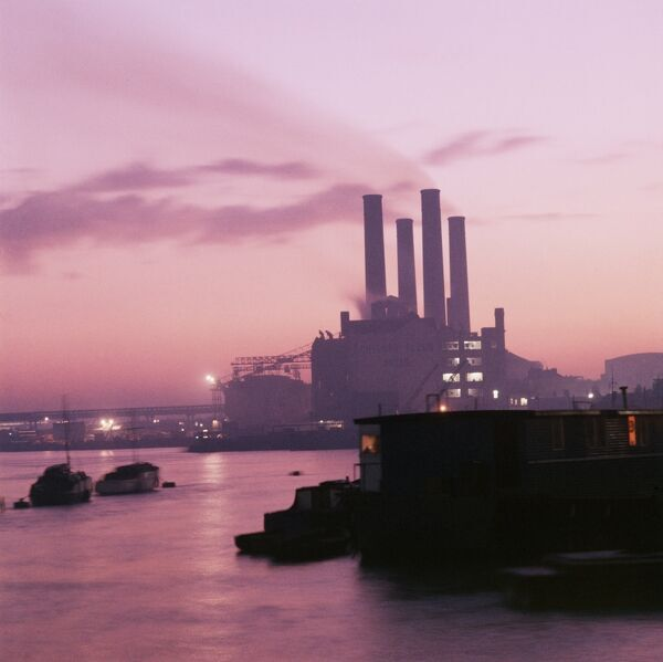 CREMORNE WHARF, Chelsea, London. View south-west along the River Thames at dusk towards Cremorne Wharf and the Chelsea Flour Mills with the Lots Road Power Station behind. Photographed by John Gay between 1955-1960