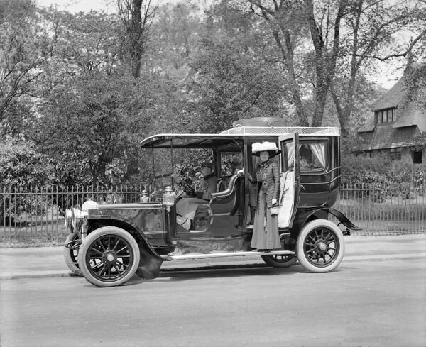 DAIMLER LIMOUSINE. Mrs Gant stands on the running board and poses for the camera by her Daimler Limousine motor car. A chauffeur sits at the wheel. Photographed by Harry Bedford Lemere, May 1909