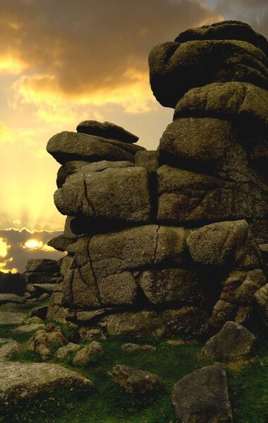 DARTMOOR, Devon. Sun setting behind clouds at Great Staple Tor