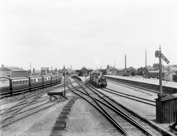 DIDCOT, Oxfordshire. Looking from the east at a signal box towards the junction station, with an engine approaching and a line of carriages to the right