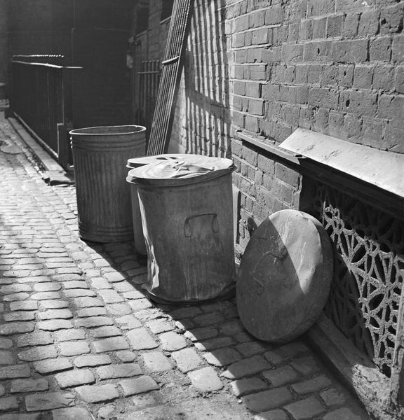 Three dustbins in a cobbled London back-street, beside an ornate iron wall grating. Photographed by John Gay. Date range 1945 - 1950
