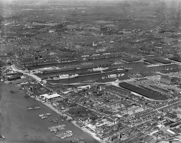 East India Docks, London. The docks and surrounding warehouses with freighters loading and unloading. Aerial view by Aeropictorial. Aerofilms Collection. July 1937