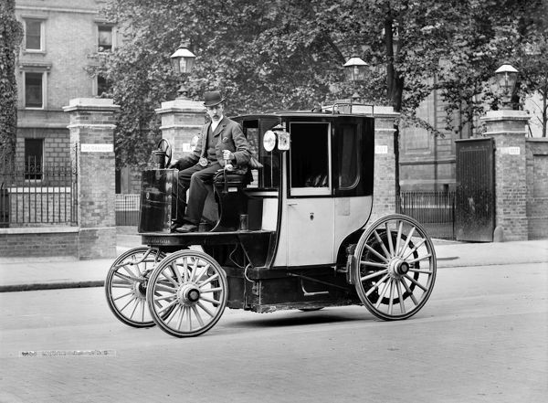 An electric motor cab and driver, London. This early cab was evidently based on the design of the horse-drawn hansom cab. Cars of any kind would have been a rare site at the time. The cab shown may be a Bersey electric cab, introduced to London in 1897