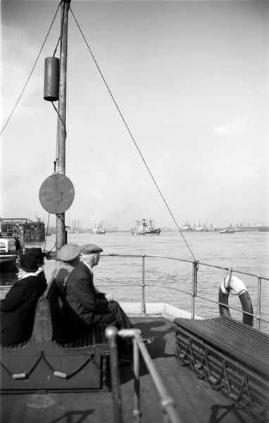 Shipping in Gravesend Reach viewed from the deck of a ferryboat with passengers in the foreground. Photographed by Stanley W Rawlings. Date range: 1945-1965
