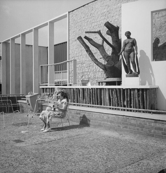 Festival of Britain, South Bank, Lambeth, London. A woman seated on a deck chair in front of the Homes and Gardens pavilion at the South Bank Exhibition during the Festival of Britain. Photographed in 1951 by M W Parry