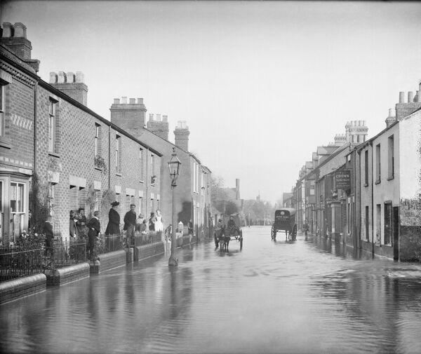 Lake Street, New Hinksey, Oxford, Oxfordshire. Looking down the street during a flood with people standing outside their houses and two carts making their way down the road. The Crown Inn is to the right. Photographed in 1890 by Henry W Taunt