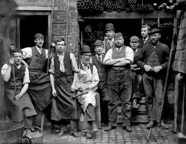 King Street, Maidenhead, Berkshire. The foundrymen of James Hews the Ironmonger's, standing in the yard of their work premises with various iron pipes in the background. Photographed by Henry Taunt. Date range: 1860-1922