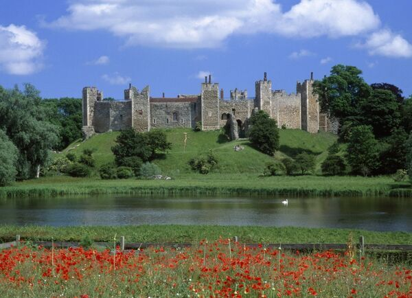 FRAMLINGHAM CASTLE, Suffolk. View looking East towards the castle from across the mere. Poppies in the foreground