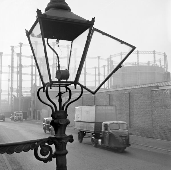 KINGS CROSS, London. A street view with an open gas street light in the foreground, a three wheeled van approaching and the gasometers at Kings Cross in the distance behind a high wall. Photographed by John Gay. Date range: 1946 - 1969