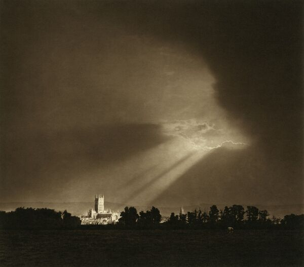 GLOUCESTER CATHEDRAL, College Green, Gloucester, Gloucestershire. Sunlight breaking through clouds and lighting the cathedral. Photographed by Sydney Pitcher between 1900 and 1920. Sun rays