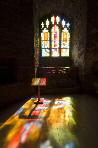 GOODRICH CASTLE, Herefordshire. Interior view of the Chapel. Stained glass window with light flooding lecturn and floor
