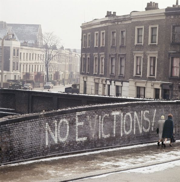GRAFTON ROAD, London. Two women walking past the graffiti 'No Evictions!' on a railway bridge on Grafton Road, Camden. Much of the area was bulldozed and redeveloped in the 1960s and early 1970s. Photographed by John Gay between 1946-1969